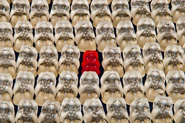 ein gummibärchen ist rot, alle anderen sind weis. das rote gummibärchen symbolisiert anders sein.