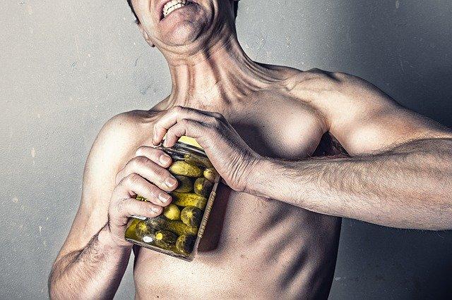 ein mensch versuchgt ein gurkenglas zu öffnen